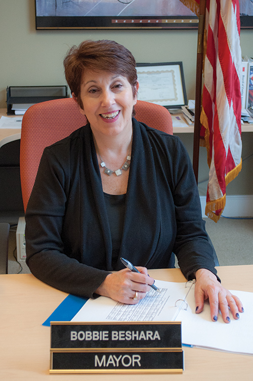 Mayor Bobbie Beshara seated at her desk, smiling while holding a pen and touching an open blue notebook